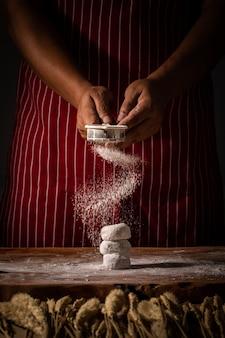 Chef propagation de la farine sur la boulangerie préparer pour la cuisson. cuisinier montrant de la poudre blanche en suspension sur une boulangerie crue maison.