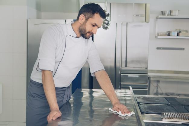 Chef de restaurant japonais masculin travaillant dans le nettoyage de la cuisine