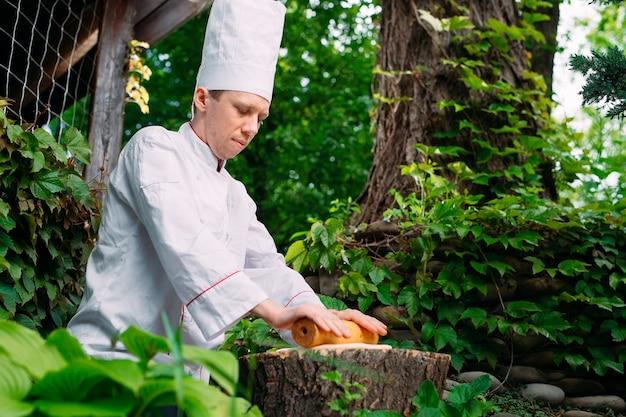 Un chef de restaurant en uniforme déroule la pâte sur une souche dans les bois