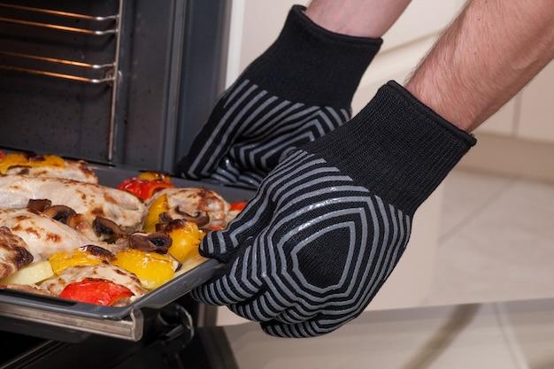 Le chef retire le plateau chaud du four avec des gants de protection