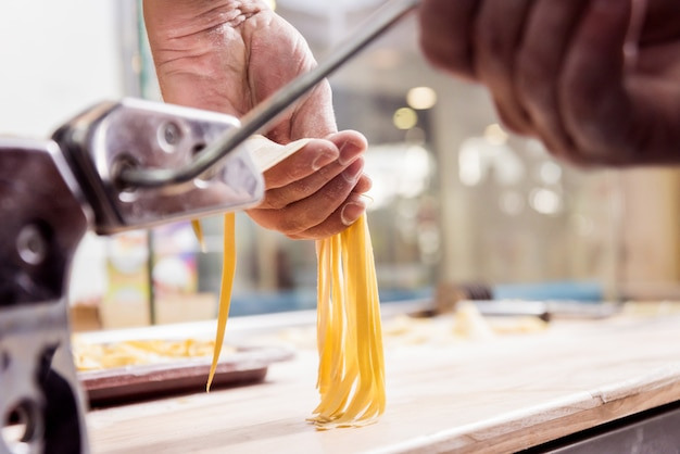 Chef roulant la pâte avec une machine à pâtes. machine à pâtes.