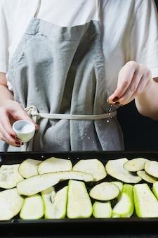 Le chef saler les tranches d'aubergines.