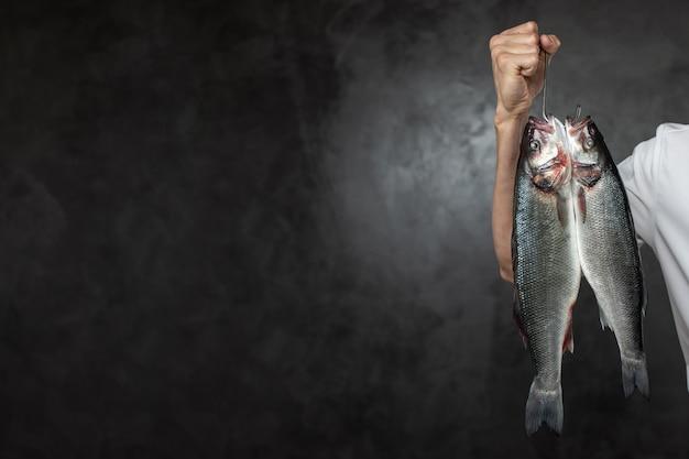 Chef sans visage tenant des poissons crus frais