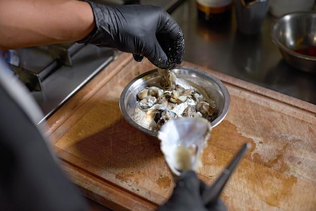 Le chef saupoudre de la farine d'huîtres fraîches à rôtir dans la cuisine,