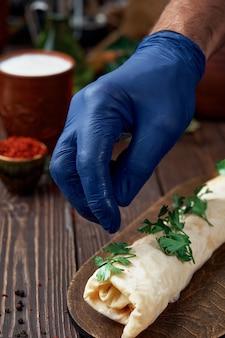 Le chef saupoudre le kebab de coriandre