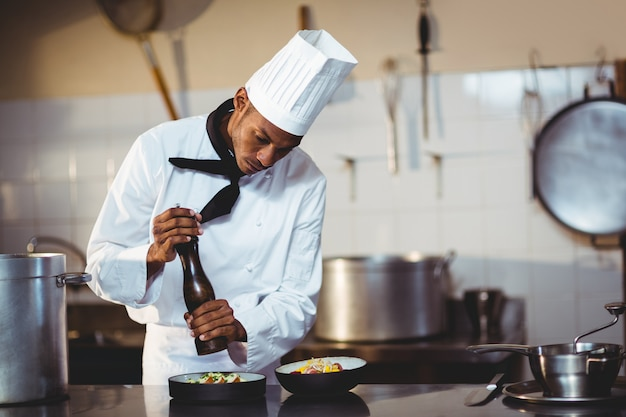 Chef saupoudrer de poivre sur un repas