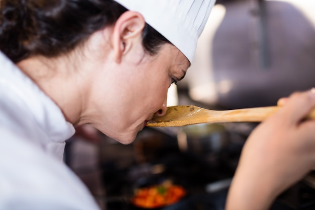 Chef sentant la nourriture dans la cuisine