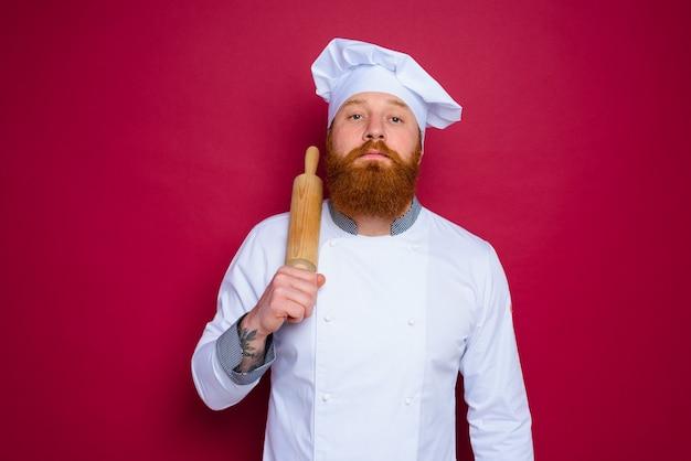 Le chef sérieux avec la barbe et le chef de tablier rouge tient le rouleau à pâtisserie en bois