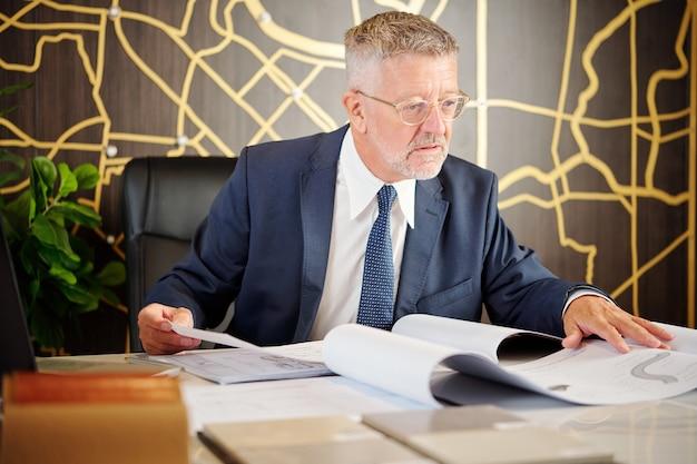 Chef sérieux du département des routes et des bâtiments vérifiant les plans de construction sur sa table