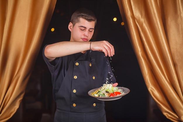 Le chef sert une salade césar avec du parmesan.