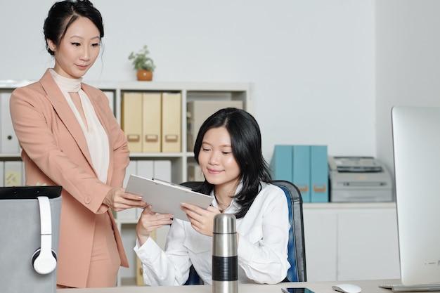Chef de service féminin donnant un document à un nouveau collègue souriant