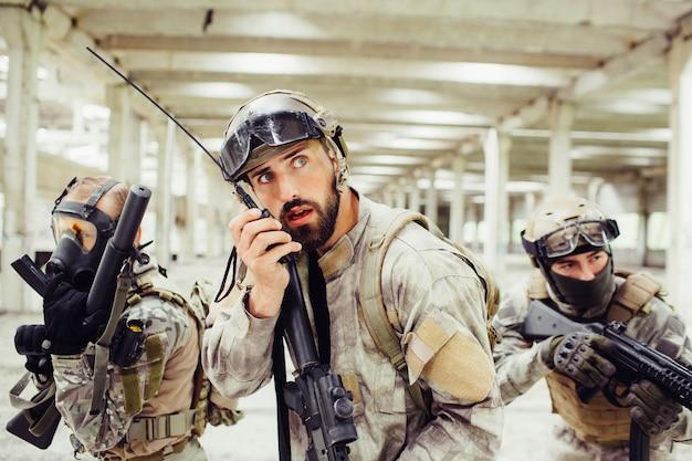 Le chef des soldats tient le fusil dans les mains et parle à une radio portable.