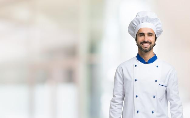 Chef souriant avec chapeau blanc