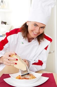 Chef souriant décorer un plat de pâtes italiennes