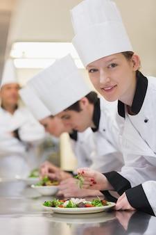 Chef souriant en levant de la préparation de la salade