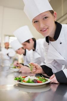 Chef souriant préparant la salade dans la classe culinaire