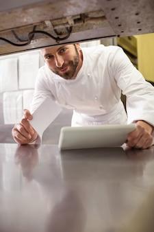 Chef souriant tenant la note de commande et la tablette numérique dans le comptoir de la cuisine
