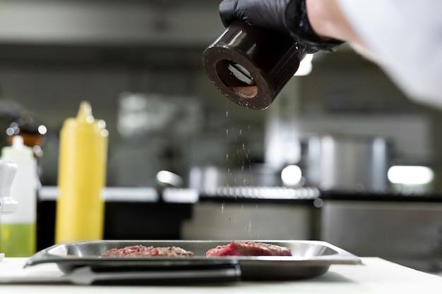 Chef steak de boeuf cru poivré. cuisinier professionnel assaisonnant la viande juteuse avec du poivre