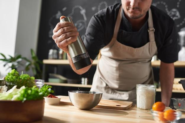Chef en tablier ajoutant du poivre dans le bol il cuisine un plat spécial à la table dans la cuisine