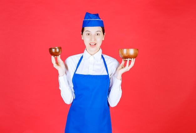 Chef en tablier bleu tenant deux tasses de thé chinois en poterie à ses deux mains.