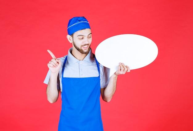 Chef en tablier bleu tenant un panneau d'information ovale et ayant une bonne idée.
