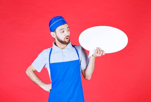 Chef en tablier bleu tenant un panneau d'information ovale et semble confus.