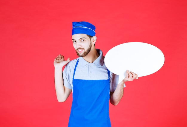 Chef en tablier bleu tenant un panneau d'information ovale.