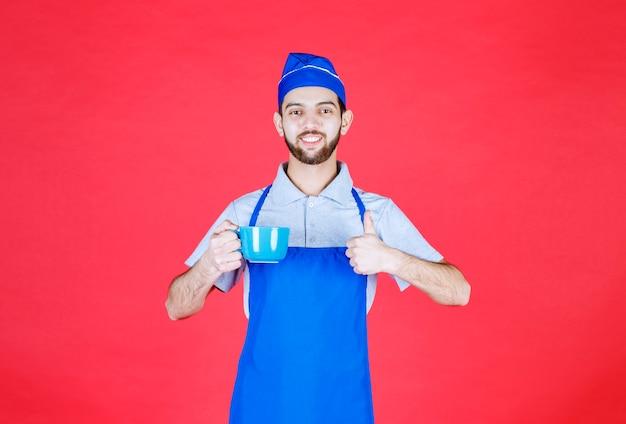 Chef en tablier bleu tenant une tasse en céramique bleue et appréciant le goût du produit.