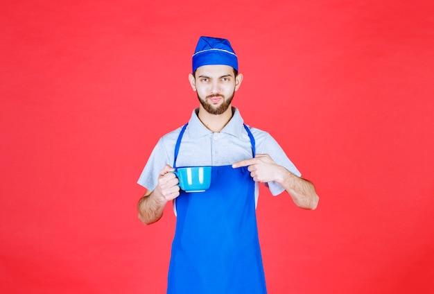 Chef en tablier bleu tenant une tasse en céramique bleue.