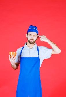 Chef en tablier bleu tenant une tasse en céramique jaune et pensant.