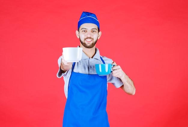 Chef en tablier bleu tenant des tasses en céramique bleue et blanche dans les deux mains et servant au client.