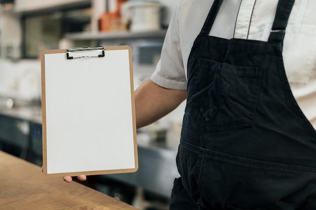 Chef avec tablier tenant le presse-papiers