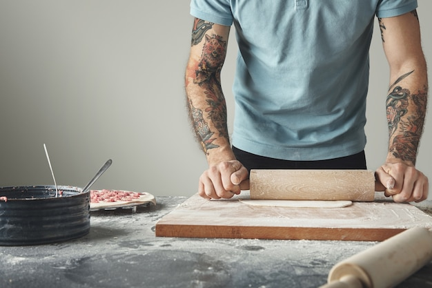 Le chef tatoué prépare des pelmeni ou des boulettes ou des raviolis dans un moule spécial.