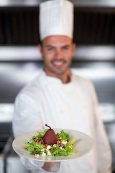 Chef tenant l'assiette dans la cuisine