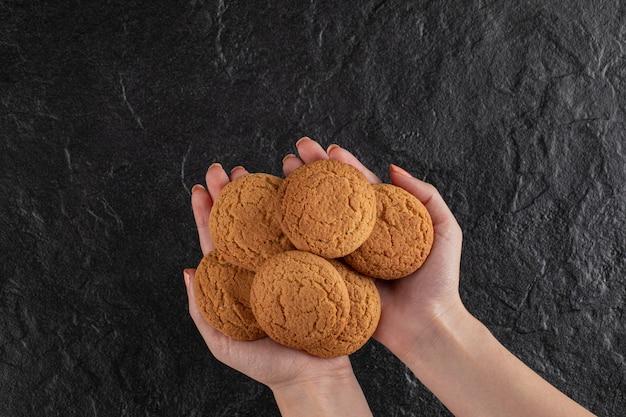 Un chef tenant des biscuits à l'avoine dans la main.