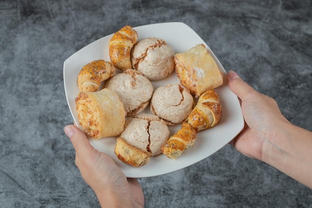 Chef tenant des biscuits croustillants avec du sucre en poudre dans la main.