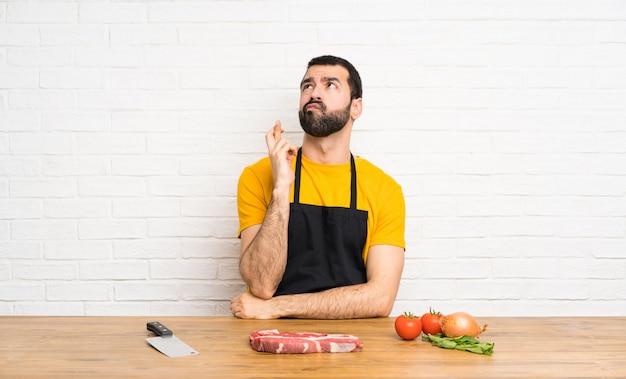 Chef tenant dans une cuisine avec les doigts qui se croisent et souhaitant le meilleur