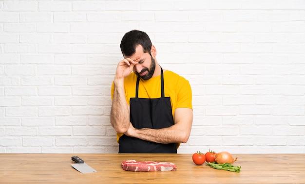 Chef tenant dans une cuisine avec une expression fatiguée et malade