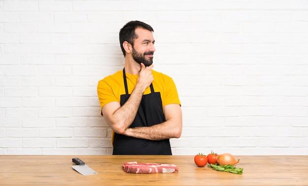 Chef tenant dans une cuisine à la recherche de côté