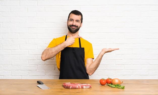 Chef tenant dans une cuisine tenant imaginaire copyspace sur la paume pour insérer une annonce
