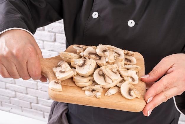 Chef tenant une planche à découper avec des champignons