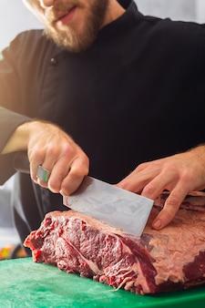 Le chef en tenue noire coupe le boeuf au couteau
