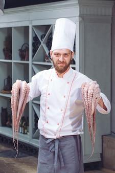 Le chef tient une pieuvre.
