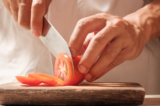 Chef de tomates coupées sur planche à découper avec couteau