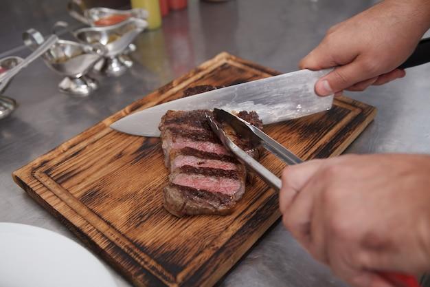 Chef tranchant le steak de boeuf sur une planche à découper en bois