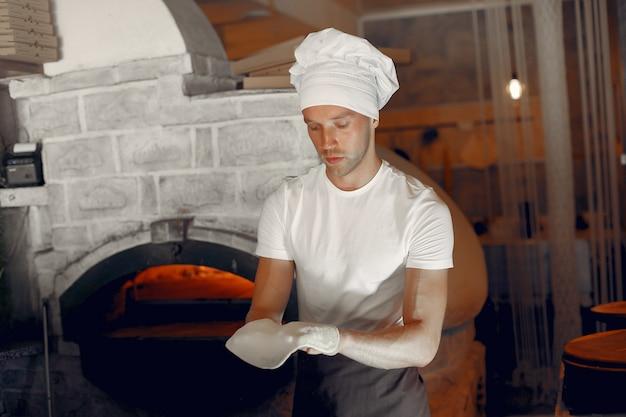 Chef en uniforme blanc prépare une pizza