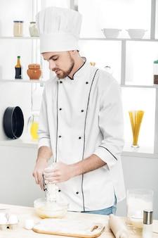 Le chef en uniforme fait de la pâte dans la cuisine
