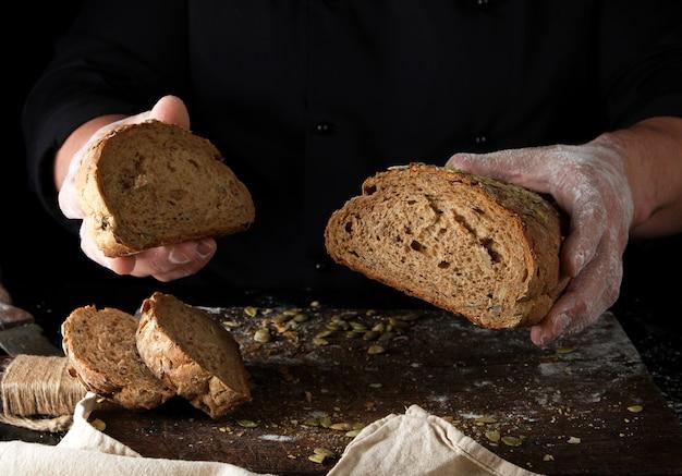 Le chef en uniforme noir garde coupé un morceau de pain cuit avec de la farine de seigle et des graines de citrouille