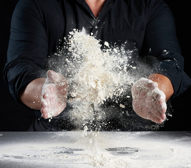 Chef en uniforme noir saupoudre la farine de blé blanc dans différentes directions, le produit disperse la poussière, fond noir, homme assis à une table