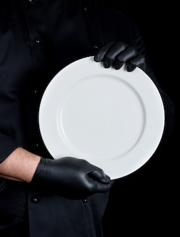 Chef en uniforme noir tenant une assiette vide ronde
